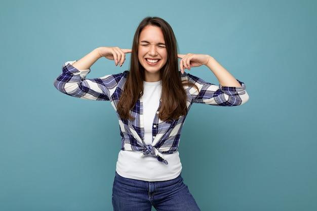 聞きたくない。チェック シャツを着た若い感情的な肯定的で笑顔の魅力的なブルネットの女性