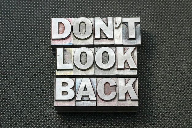 Don't look back phrase made from metallic letterpress blocks on black perforated surface