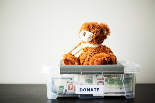 Donate box with dollars on wooden desk