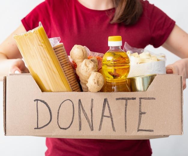 白い背景の上の女性の手に食べ物、食料品が入った箱を寄付します。ボランティアは、19回の検疫中に出前を行います。支援、外出禁止令、コロナウイルスの自己隔離。