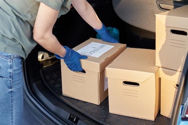 寄付とボランティアのコンセプト。車のトランクの手袋のロードボックスの女性。