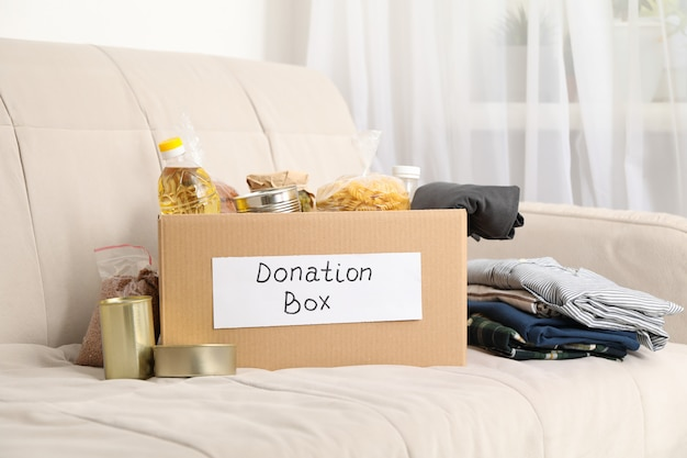 Donation box. food and clothes on sofa. volunteering