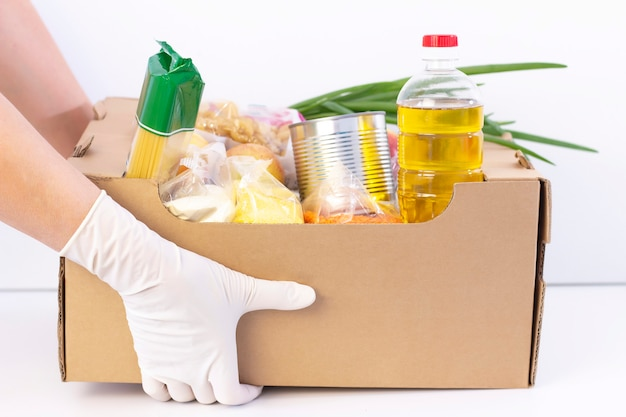 Donation box. in hands in rubber gloves is a cardboard box with food on a white surface.