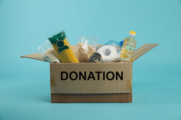 Donation box. open cardboard box with clothes and food on a blue background. charity concept.