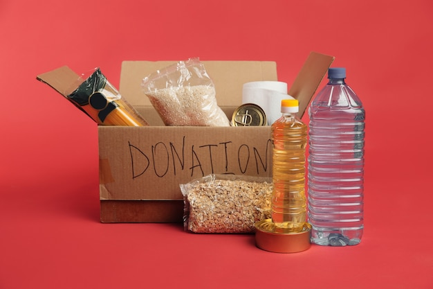 Donation box. open cardboard box with clothes and food on a red background