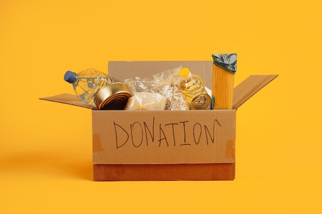 Donation box. open cardboard box with clothes and food on a yellow background.
