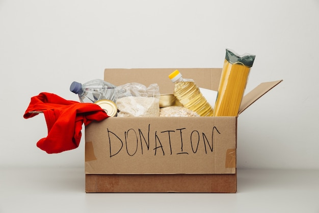 Donation box. open cardboard box with clothes and food.