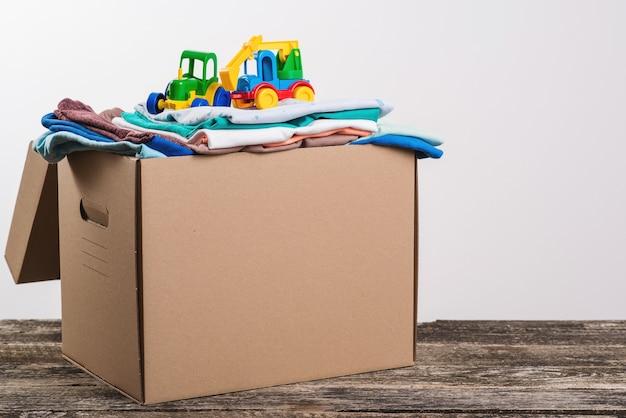 Ящик для пожертвований с детскими вещами и игрушками. ящик для пожертвований заполнен вещами для пожертвования. помогите бедным.