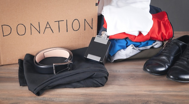 Donation box with clothes on the wooden table.