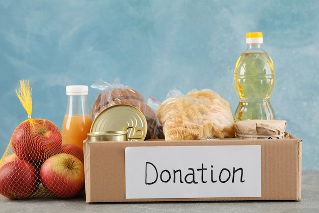 Donation box with different food on gray table. volunteering