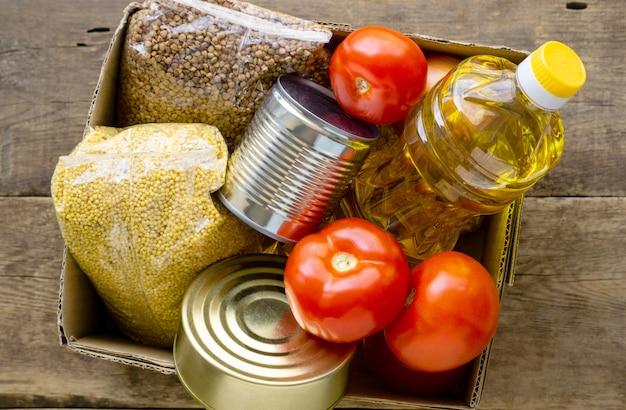 Ящик для пожертвований с различными продуктами на деревянном фоне