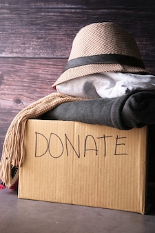Donation box with donation clothes on a wooden table .