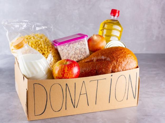 食物と一緒に募金箱。食料品は灰色の背景に設定します。寄付のコンセプト