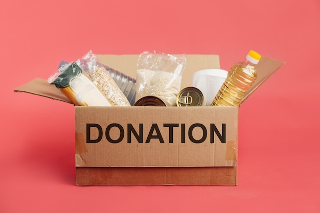 Donation box with food isolated on red background.