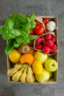 Donation box with fresh organic fruits, vegetables and herbs on a concrete background. proper nutrition. delivery healthy food to the home.
