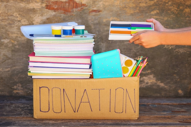 Donation box with school supplies on old wooden table