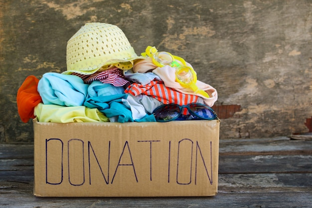 Donation box with summer clothes on the old wooden background.