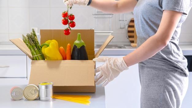 スーパーフードの果物と野菜の募金箱。食品のコンセプトを共有しています。食品配達。食料を集めるボランティア。コロナウイルスのパンデミックヘルプ