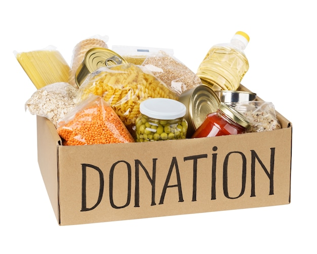Donation box with various food. open cardboard box with oil, canned food, cereals and pasta. isolated.