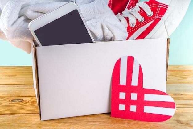 붉은 하트 로고가 있는 기부 화요일을 위한 다양한 기부 상품이 있는 기부 상자. 자선 단체. 원치 않는 폐기물을 수집하고 가난한 사람들의 개념을 전달하십시오. 국제 기부 캠페인에 참여합니다.
