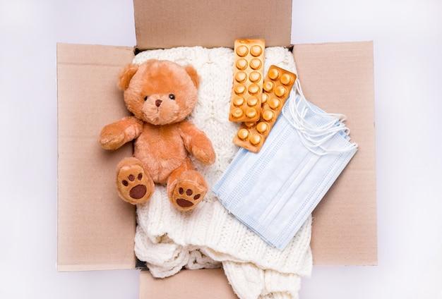 Концепция пожертвования. пакет ухода, в котором игрушки, лекарства, предметы и средства индивидуальной защиты