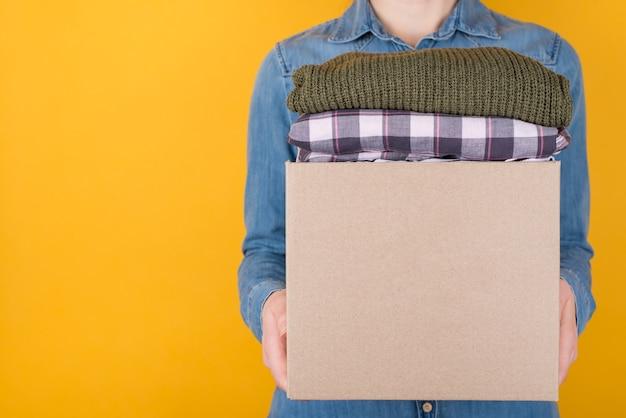 寄付のコンセプト。黄色の背景に分離された寄付するために服でいっぱいの箱を持っている女性の側面のトリミングされた写真を閉じる