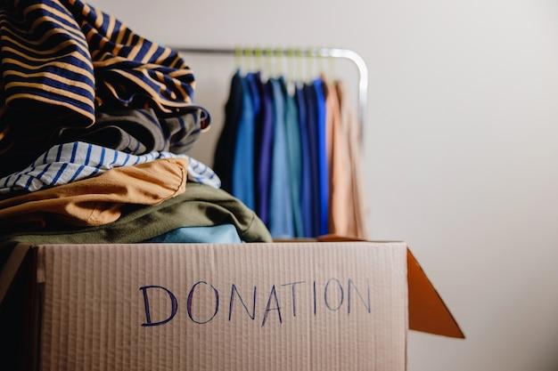 Концепция пожертвования. подготовка старой старой одежды из гардеробной в ящик для пожертвований. сосредоточьтесь на тексте