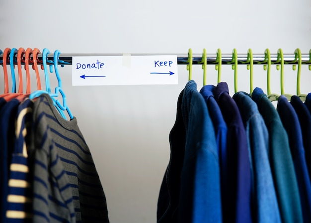 Donation concept. separated used old clothes from wardrobe rack to keep and donate. focus on text