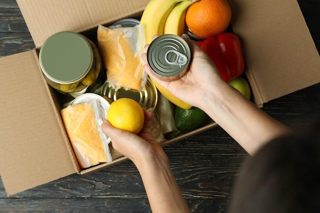 소녀와 기부 개념은 상자에 식료품을 넣습니다.