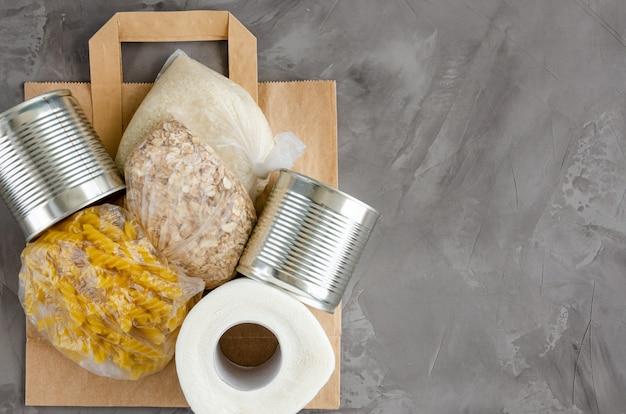 Пожертвование еды. бумажный пакет с консервами, макаронами, овсянкой, рисом и туалетной бумагой на темном фоне бетона. доставка еды. горизонтальный, вид сверху, копия пространства.