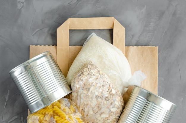 Пожертвование еды. бумажный пакет с консервами, макаронами, овсянкой, рисом и туалетной бумагой на темном фоне бетона. доставка еды.