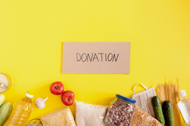 Donation. food supplies crisis food stock for quarantine isolation period on yellow background. rice, peas, cereals, canned food, oil, vegetables, mask, sanitizer. food delivery, coronavirus.