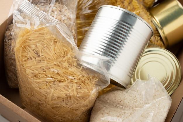 お金や仕事のない人のための寄付。ボックスに入った一連の製品-パスタ、バター、オートミール