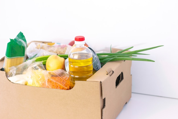 Donation. grocery box, help products to those in need. donation box. cardboard box with food essentials on a white surface.