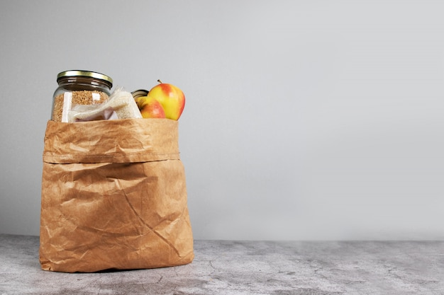 Donation paper bag food supplies for people in isolation on a gray background with copy space. food delivery