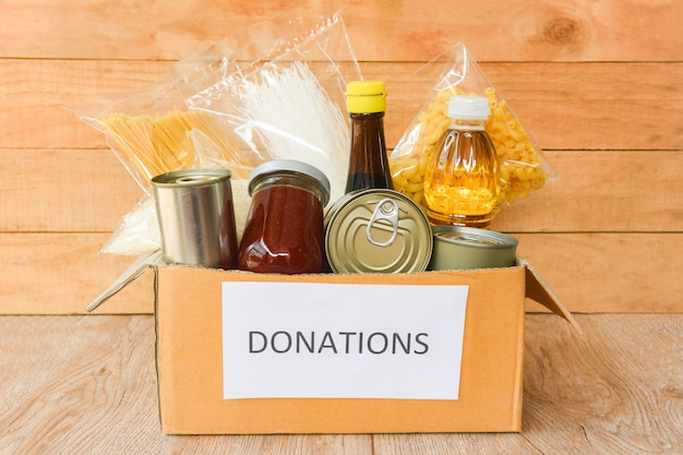 Donations box with canned food on wooden table background / pasta canned goods and dry food non perishable with cooking oil rice noodles spaghetti macaroni donations food
