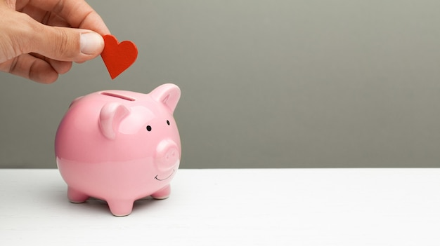 Donations of love and feelings, sympathy. man puts heart in piggy bank. copy space for text.
