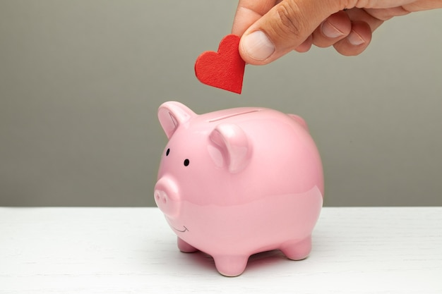 Donations of love and feelings, sympathy. man puts heart in piggy bank.