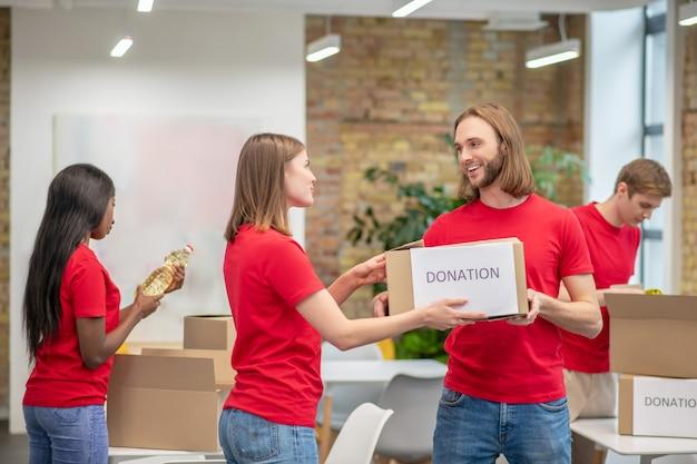 기부, 자원 봉사자. 좋은 분위기의 자선 센터에서 기부 상자를 포장하는 젊은 참여 세심한 자원 봉사자의 그룹