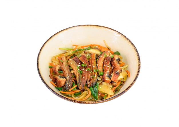 Donburi unagi or eel slices with rice, vegetables in ceramic bowl