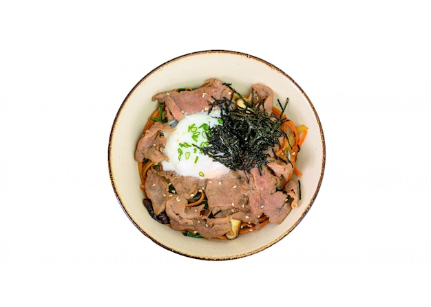 Donburi wagyu beef slices with onsen egg, rice, vegetables in ceramic bowl