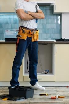 立っているツールベルトを身に着けている若い修理工のプロの配管工の右のトリミングされたショットを行いました