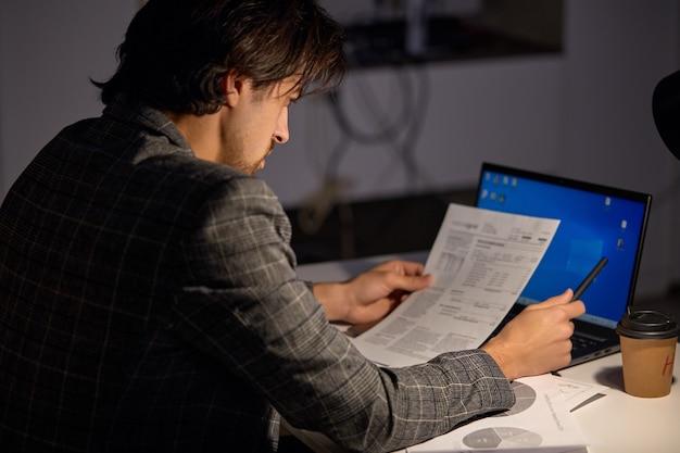 마감일까지 완료되었습니다. 사무실에서 혼자 일하는 남자, 늦은 밤까지 머물고 있습니다. 젊은 사업가, 노트북 및 서류 작업 관리자, 복사 공간. 비즈니스, 마감, 네트워킹 개념입니다. 측면보기