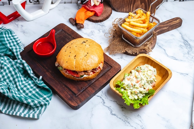Doner nel pane con ketchup su una tavola con patatine fritte e insalata di capitale