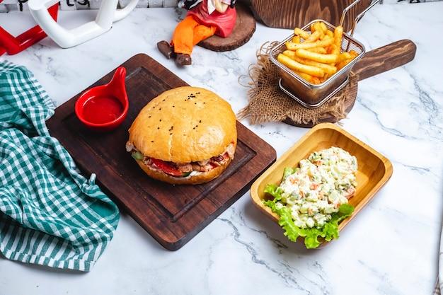 Донер в хлебе с кетчупом на доске с картофелем фри и столичным салатом