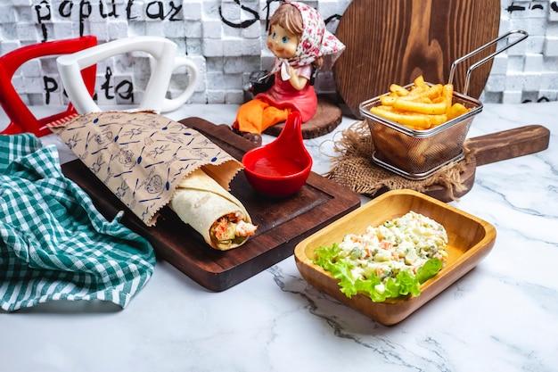 Донер в лаваше с кетчупом на доске с картофелем фри и салатом в столице