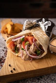 新鮮な野菜や肉の穴にあるシャワルマ、ドネルケバブ。大きなスパイスで。レストランでお召し上がりいただけます。暗い背景に。メニューと広告用