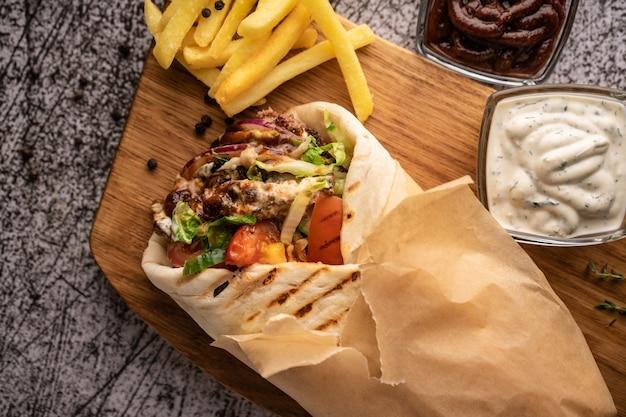 Донер-кебаб - шаурма в косточке из свежих овощей и мяса с большим рестораном специй, который подают на ...