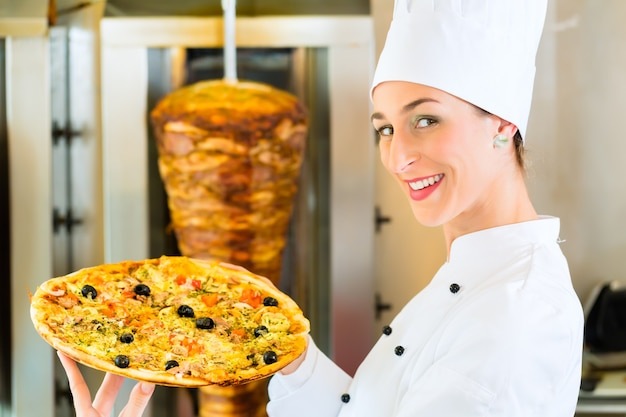 Doner 케밥-꼬치 앞에서 피자를 들고있는 터키 식 패스트 푸드 식당의 친절한 여성 공급 업체
