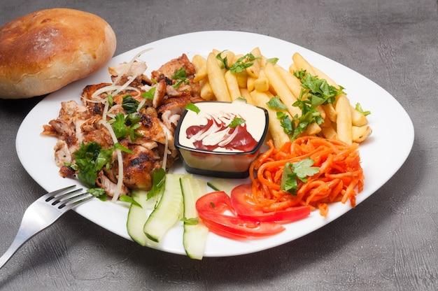 Донер кебаб или шаурма на тарелке с картофелем фри